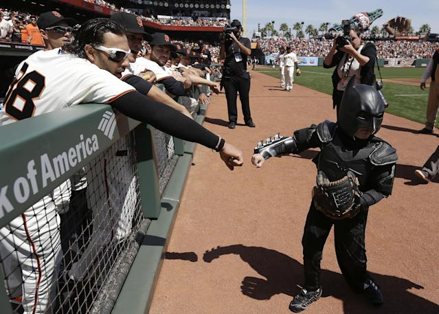 Miles Scott, right, dressed as Batkid, is greeted by San Francisco Giants left fielder Michael Morse after throwing the ceremonial first pitch before the Giants' home-opener baseball game against the Arizona Diamondbacks in San Francisco, Tuesday, April 8, 2014. On Nov. 15, 2013, Miles a Northern California boy with leukemia, fought villains and rescued a damsel in distress whiled dressed as a caped crusader through The Greater Bay Area Make-A-Wish Foundation. (AP Photo/Eric Risberg, Pool)