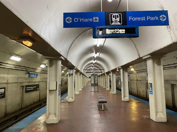a completely empty subway station in Chicago with signs hanging above