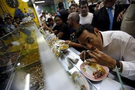 Guatemalan presidential candidate Jimmy Morales (R) eats lunch at the central market in Guatemala City, October 21, 2015.  REUTERS/Jorge Dan Lopez