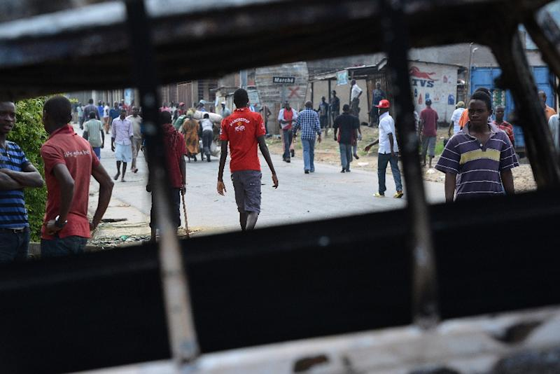 Burundian youths walk in the street during a demonstration against the president's bid for a third term on May 1, 2015, in Bujumbura (AFP Photo/Simon Maina)