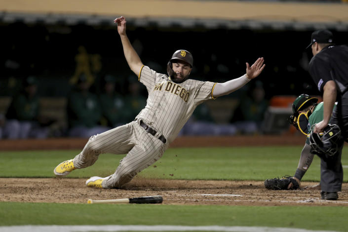 San Diego Padres' Eric Hosmer, left, scores on a single by Trent Grisham, in front of Oakland Athletics catcher Yan Gomes, right, during the seventh inning of a baseball game in Oakland, Calif., Tuesday, Aug. 3, 2021. (AP Photo/Jed Jacobsohn)
