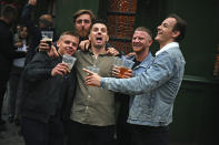 Men pose for a photo, outside a pub as it reopened, in Borough Market, as coronavirus lockdown restrictions eased across England, in London, Saturday July 4, 2020. England embarked on perhaps its biggest lockdown easing yet as pubs and restaurants reopened for the first time in more than three months. (Victoria Jones/PA via AP)