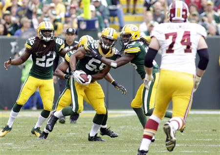 Green Bay Packers linebacker Brad Jones (C) gets a fumble recovery during the second half of their NFL football game against the Washington Redskins in Green Bay, Wisconsin September 15, 2013. The Packers defeated the Redskins 38-20. REUTERS/Darren Hauck