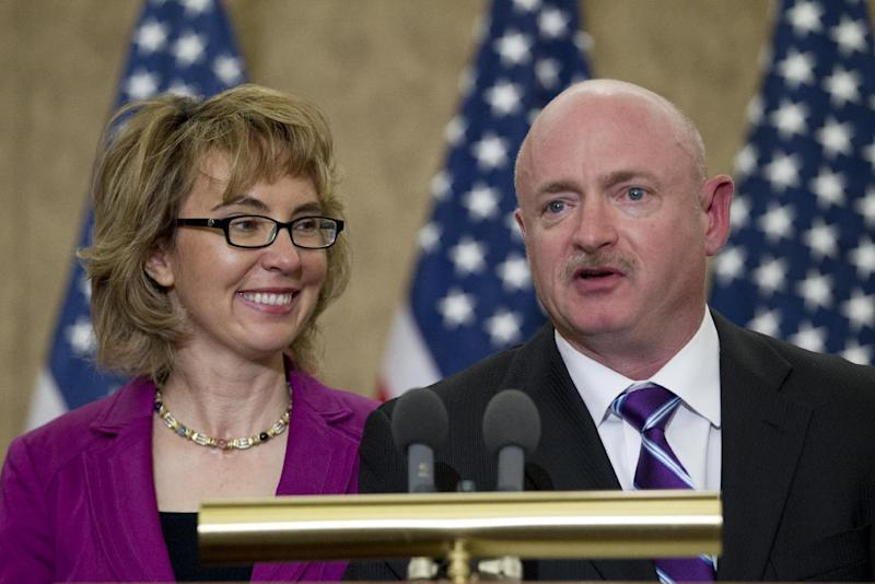 "Former Arizona Rep. Gabrielle Giffords listens as her husband, retired astronaut Mark Kelly speaks on Capitol Hill, in Washington, Tuesday,  April 16, 2013, during a ceremony to honor Gabriel ""Gabe"" Zimmerman.  Zimmerman was Giffords' outreach director until he was killed in the January 2011 shooting rampage in Tucson where Giffords was wounded.  (AP Photo/Jose Luis Magana)"