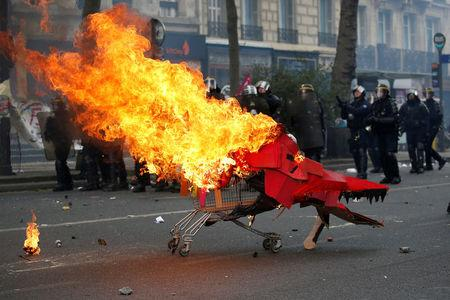 Flames from a burning cardboard dragon in a caddy are seen near French CRS riot police during clashes as part of the traditional May Day labour union march in Paris. REUTERS/Gonzalo Fuentes