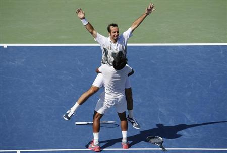 Leander Paes lifts playing partner Radek Stepanek of the Czech Republic after they defeated Alexander Peya of Austria and Bruno Soares of Brazil in their men's doubles final match at the U.S. Open tennis championships in New York September 8, 2013. REUTERS/Ray Stubblebine