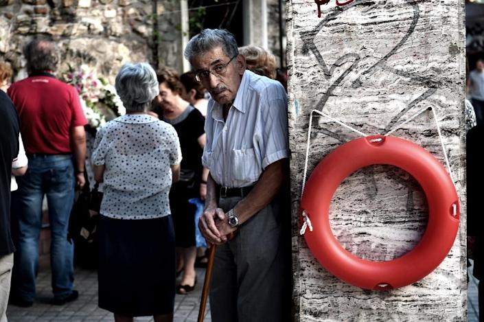 An elderly man stands outside a chapel in central Athens, on July 7, 2015 (AFP Photo/Aris Messinis)