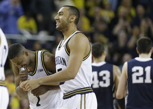 Michigan forward Glenn Robinson III, left, and forward Jon Horford walk back to the bench after defeating Penn State in an NCAA college basketball game at Crisler Center in Ann Arbor, Mich., Sunday, Feb. 17, 2013. (AP Photo/Carlos Osorio)