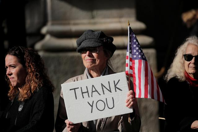 A woman holds a sign as she watches the Veterans Day parade in New York on Nov. 11, 2019. (Photo: Brendan McDermid/Reuters)