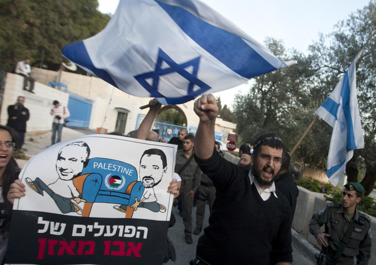 """Israeli right wing activists demonstrate against the Palestinian U.N. bid for observer state status, in front of the U.N. headquarters in Jerusalem, Thursday, Nov. 29, 2012. The Palestinians are certain to win U.N. recognition as a state on Thursday but success could exact a high price: delaying an independent state of Palestine because of Israel's vehement opposition. Hebrew on sign reads: """"Abu Mazen's workers."""" (AP Photo/Sebastian Scheiner)"""
