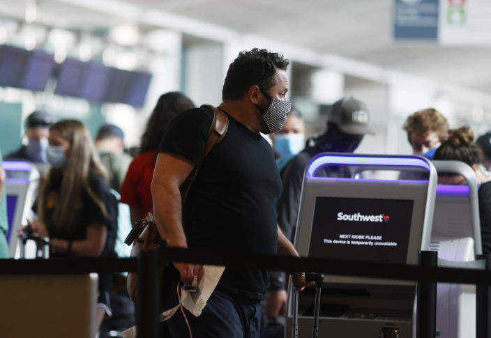 A traveler wears a face mask while heading to a check-in kiosks for Southwest Airlines in the main terminal of Denver International Airport late Monday, June 22, 2020, in Denver during the coronavirus pandemic. (AP Photo/David Zalubowski)