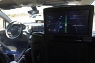A Waymo minivan moves along a city street as an empty driver's seat and a moving steering wheel drive passengers during an autonomous vehicle ride, as passengers view a detailed viewing screen, Wednesday, April 7, 2021, in Chandler, Ariz. Waymo, a unit of Google parent Alphabet Inc., is one of several companies testing driverless vehicles in the U.S. But it's the first offering lifts to the public with no humans at the wheel who can take over in sticky situations. (AP Photo/Ross D. Franklin)