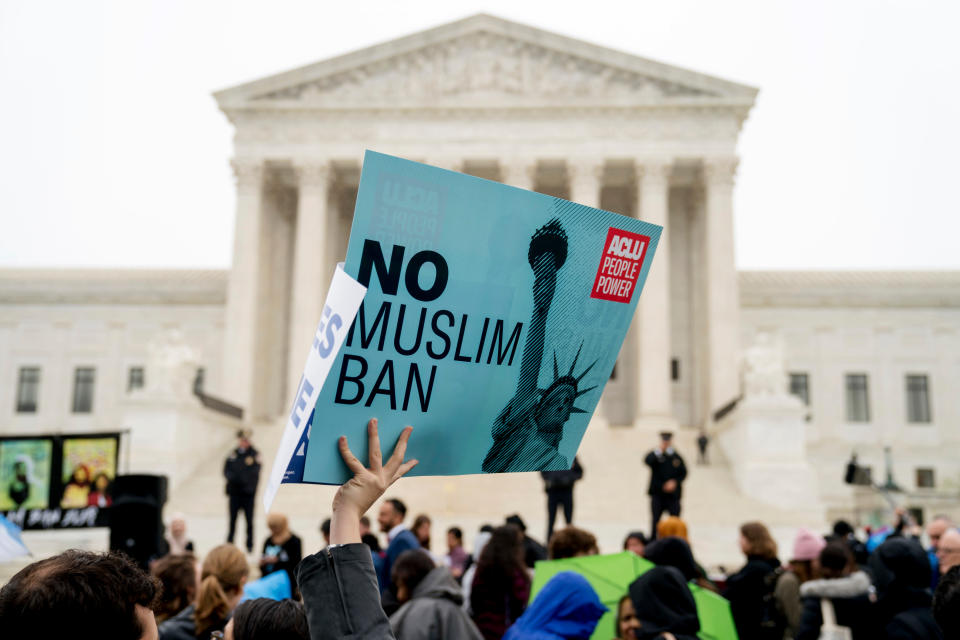 """FILE - In this April 25, 2018, file photo, a person holds up a sign that reads """"No Muslim Ban"""" during an anti-Muslim ban rally as the Supreme Court hears arguments about whether President Donald Trump's ban on travelers from several mostly Muslim countries violates immigration law or the Constitution in Washington. Six of Biden's 17 first-day executive orders dealt with immigration, such as halting work on a border wall in Mexico and lifting a travel ban on people from several predominantly Muslim countries. (AP Photo/Andrew Harnik, File)"""