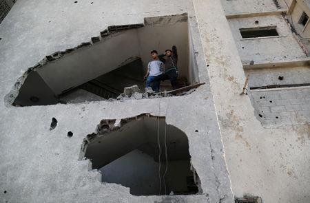 Palestinians look out of their house that was damaged in an Israeli air strike, in Gaza City November 13, 2018. REUTERS/Suhaib Salem