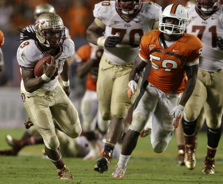Florida State running back Devonta Freeman (8) runs for a first down past Miami linebacker Jimmy Gaines (59) during the second half of an NCAA college football game, Saturday, Oct. 20, 2012, in Miami. (AP Photo/Lynne Sladky)
