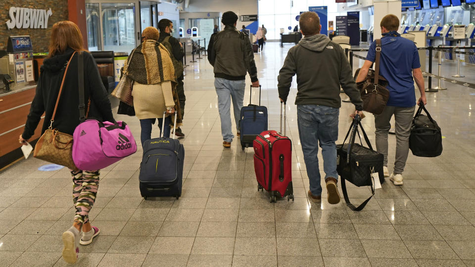 Travelers walk through the terminal at Cleveland Hopkins International Airport before boarding a plane, Wednesday, Nov. 25, 2020, in Cleveland. (AP Photo/Tony Dejak)
