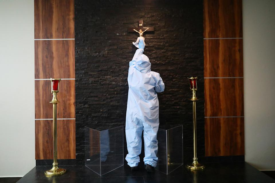 An employee wearing protective clothing disinfects a crucifix at Funeral Gayosso, as the outbreak of the coronavirus disease (COVID-19) continues in Mexico City, Mexico May 11, 2020. Picture taken May 11, 2020. REUTERS/Edgard Garrido