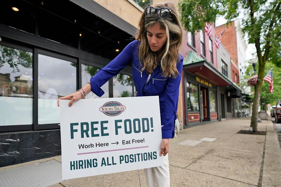 """Coleen Piteo, director of marketing at Yours Truly restaurant, puts out a sign that says, """"Free Food"""" and """"Hiring all positions"""" to lure in job applicants."""