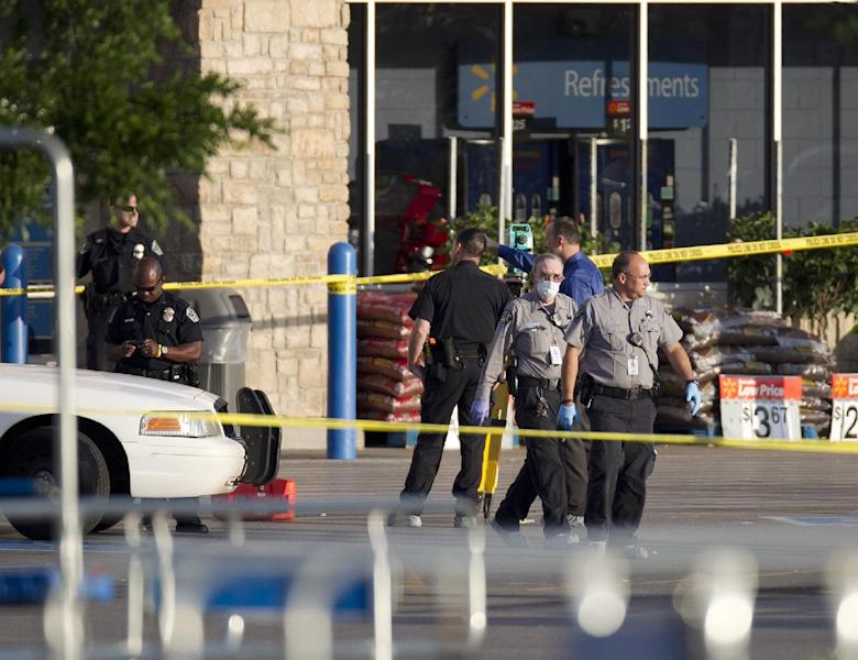 Austin Police Department personnel work the scene of a shooting at a Walmart in the early morning hours of Friday, April 6, 2012 in Austin, Texas. A police officer was shot and killed early Friday at a Walmart in Central Texas, and a suspect is in custody, police said. Austin Police Chief Art Acevedo said the officer was shot in the neck and died at the scene. The department identified him as Senior Police Officer Jaime Padron and said he had two daughters, ages 10 and six. Padron was responding to a call about a drunk man inside the store around 2:30 a.m., Acevedo said. The suspect attacked the officer as soon as he arrived at the store and Padron didn't have a chance to even pull out his own weapon. (AP Photo/Austin American-Statesman, Deborah Cannon) MAGS OUT; NO SALES; INTERNET AND TV MUST CREDIT PHOTOGRAPHER AND STATESMAN.COM