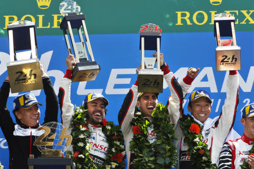 Drivers of the Toyota TS050 Hybrid No8 of the Toyota Gazoo Racing Team Sebastien Buemi of Switzerland, second from right, Fernando Alonso of Spain, second from left, and Kazuki Nakajima of Japan, right, celebrate with their trophy after winning the 86th 24-hour Le Mans endurance race, in Le Mans, western France, Sunday, June 17, 2018. (AP Photo/Thibault Camus)