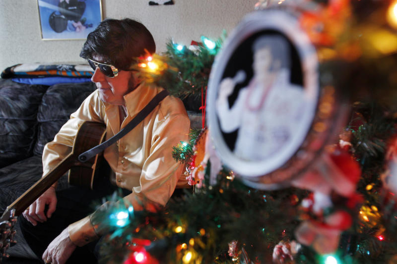 Ted Prior, 67, dressed as Elvis Presley, holds a guitar as he sits in his home Wednesday, Dec. 29, 2010, in Galloway Township, N.J. This New Year's Eve, for the first time he can remember, Prior won't be gyrating on a stage somewhere, warning someone not to step on his blue suede shoes. Cancer that has spread throughout his body is forcing Prior to miss a scheduled concert in Ocean City — it's the first time in a 50-year career spanning nearly 10,000 performances that south Jersey's answer to The King has had to miss a show. (AP Photo/Mel Evans)