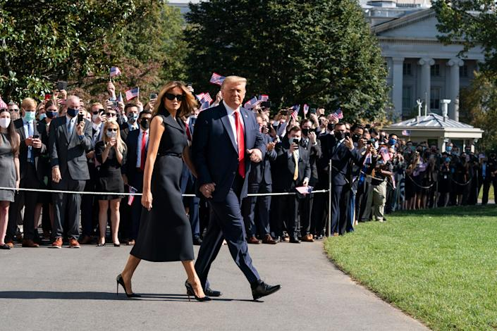 President Donald Trump gives thumbs up, accompanied by first lady Melania Trump, as they walk to board Marine One on the South Lawn of the White House on Oct. 22, 2020, in Washington. Trump is headed to Nashville, Tennessee, for a debate.