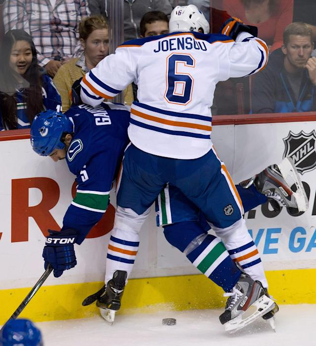 Edmonton Oilers' Jesse Joensuu, right, of Finland, checks Vancouver Canucks' Jason Garrison during the second period of a preseason NHL hockey game Wednesday, Sept. 18, 2013, in Vancouver, British Columbia. (AP Photo/The Canadian Press, Darry Dyck)