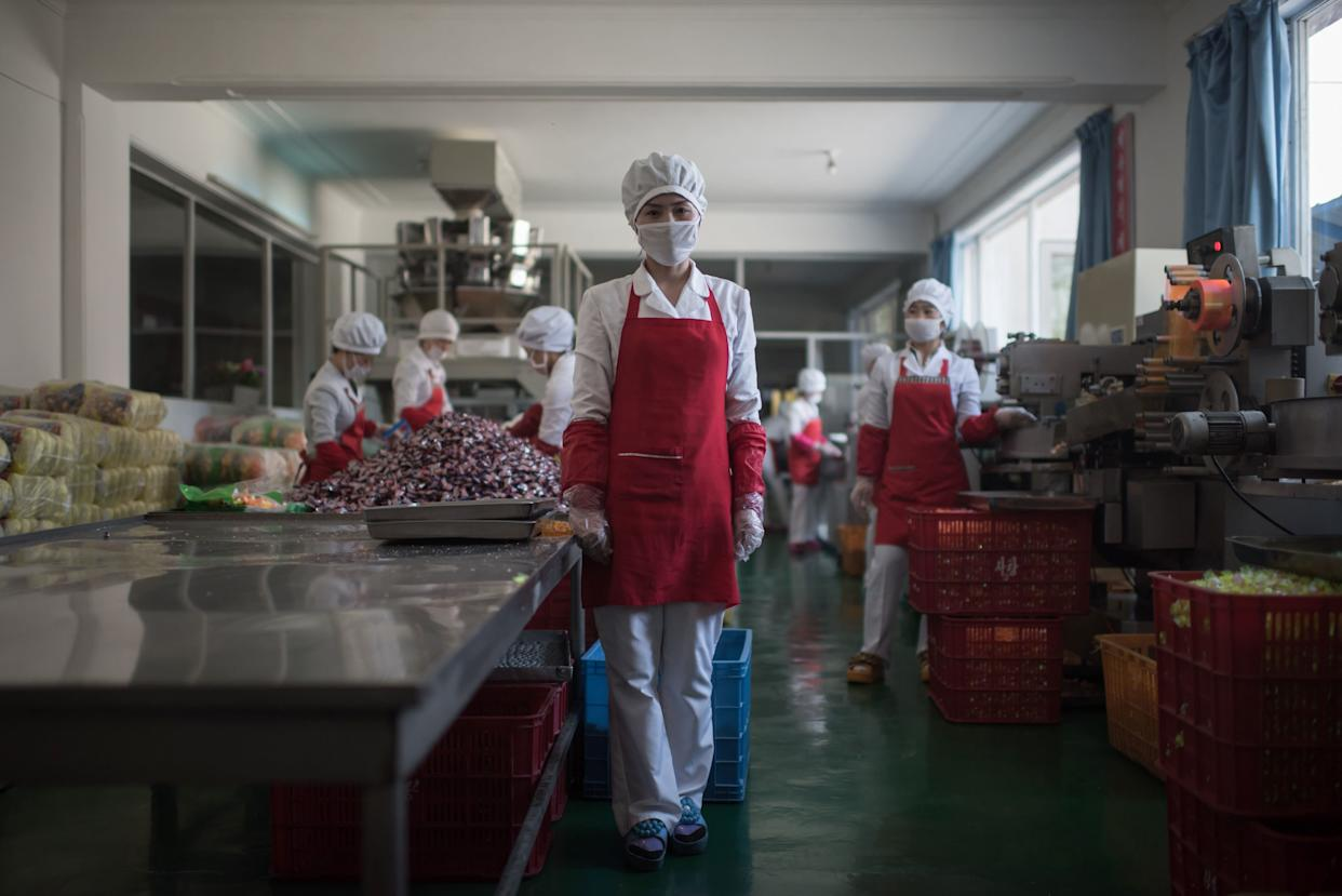 Hong Kum-Ju, 27, poses for a portrait at the food factory where she works, in the eastern port city of Wonsan.
