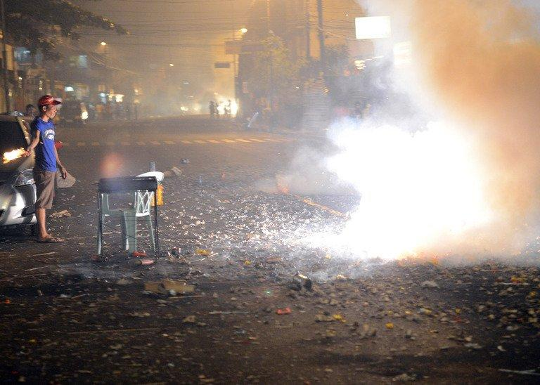 Revellers set off firecrackers to usher in New Year's Day in Manila, on January 1, 2013