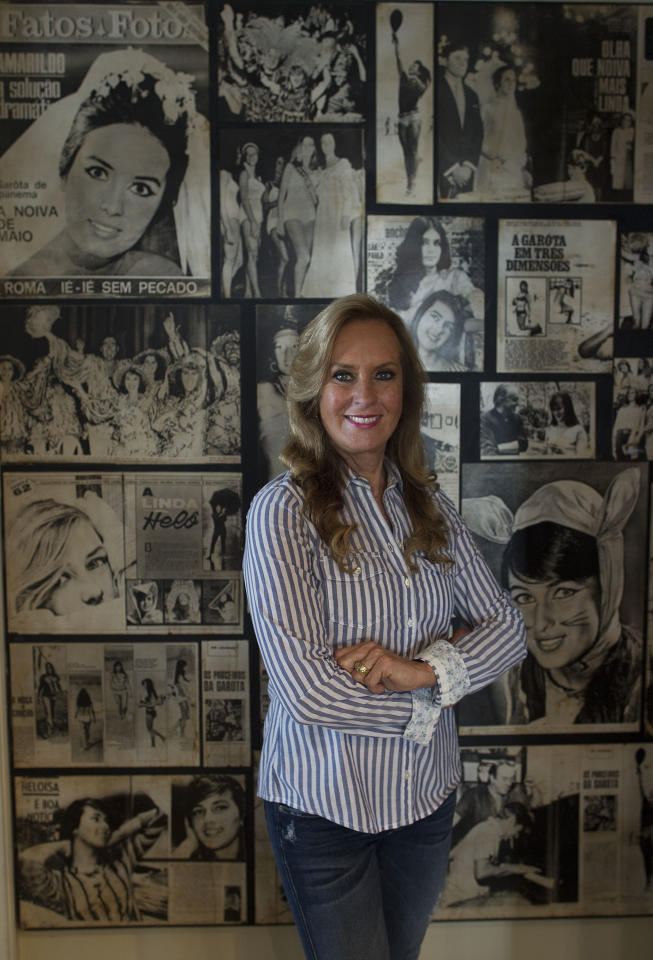 """In this July 3, 2012 photo, Heloisa """"Helo"""" Pinheiro, the woman that inspired the classic bossa nova song, """"The Girl From Ipanema,"""" poses for a photo backdropped by a collage of pictures from her youth, in Sao Paulo, Brazil. The quintessential tune was inspired by Pinheiro when she passed the songwriters in a beach side bar on her way to the sea, 50 years ago. To its legions of fans, the decades have only heightened the song's allure, adding a wash of nostalgia to this hymn to passing youth and beauty. At 68, Pinheiro has two TV shows roles and is planning to launch a book in English about her past. (AP Photo/Andre Penner)"""