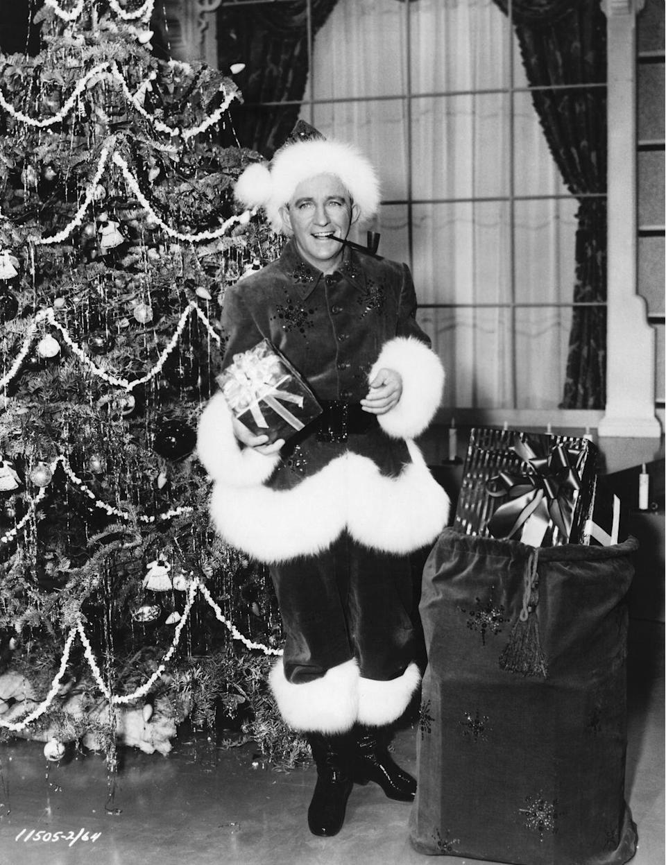 <p>The talented singer/actor dons a Santa suit and smoking pipe as he poses in front of a Christmas tree to promote his holiday musical film, Paramount's <em>White Christmas </em>(1954).<br></p>