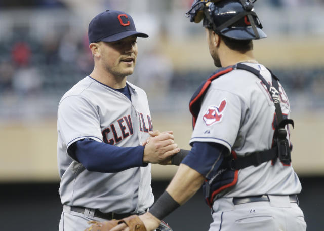 Cleveland Indians pitcher Joe Smith, left, and catcher Yan Gomes celebrate as the Indians beat the Minnesota Twins 5-1 in a baseball game, Saturday, Sept. 28, 2013, in Minneapolis. (AP Photo/Jim Mone)