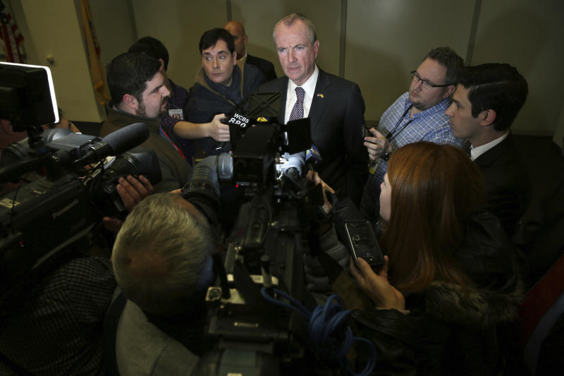 "FILE - In this Monday, Dec. 11, 2017 file photo, New Jersey Governor-elect Phil Murphy, center, answers a question as he is surrounded by media in Newark, N.J. In the wake of the new federal tax plan, some leaders have indicated they'll explore legal challenges to it. ""I'm certainly not a constitutional lawyer, but the notion that this is not constitutional is something we want to pursue,"" says the governor-elect. (AP Photo/Mel Evans)"