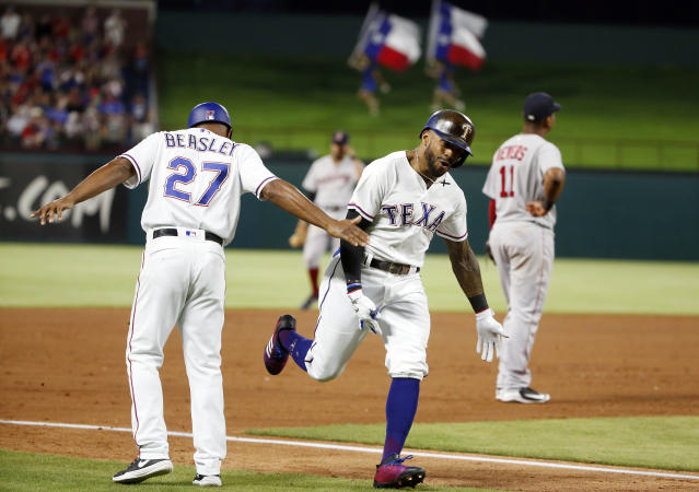 Texas Rangers third base coach Tony Beasley (27) congratulates Delino DeShields as Boston Red Sox third baseman Rafael Devers (11) looks away after DeShields hit a three-run home run during the fifth inning of a baseball game Saturday, May 5, 2018, in Arlington, Texas. (AP Photo/Michael Ainsworth)