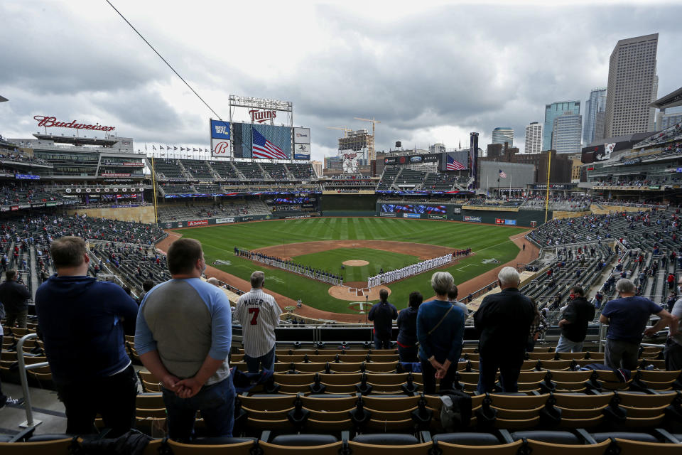 The Seattle Mariners and Minnesota Twins stand along the baselines and fans stand for the national anthem for the home opener baseball game at Target Field Thursday, April 8, 2021, in Minneapolis. Due to COVID-19 restrictions, only 10,000 fans are allowed in the ballpark. (AP Photo/Bruce Kluckhohn)