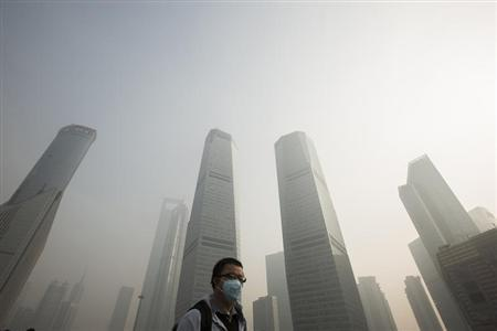 A man wears a mask while walking on a bridge during a hazy day in Shanghai's financial district of Pudong