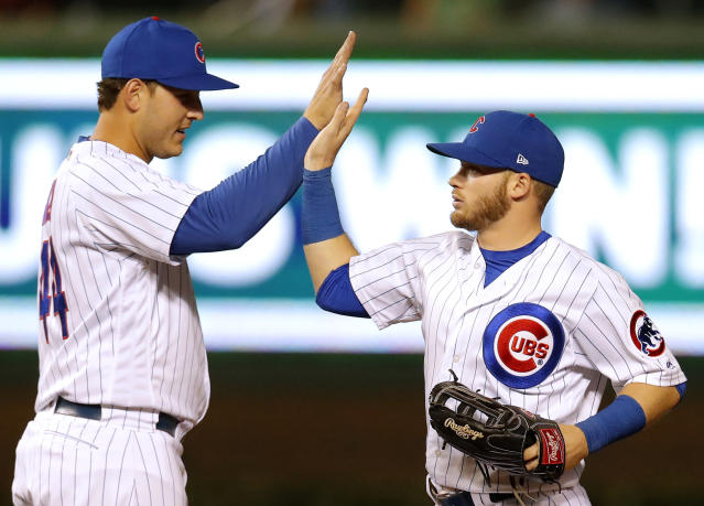 Chicago Cubs' Anthony Rizzo, left, and Ian Happ celebrate their win over the Cincinnati Reds at the end of a baseball game Friday, Sept. 14, 2018, in Chicago. (AP Photo/Jim Young)