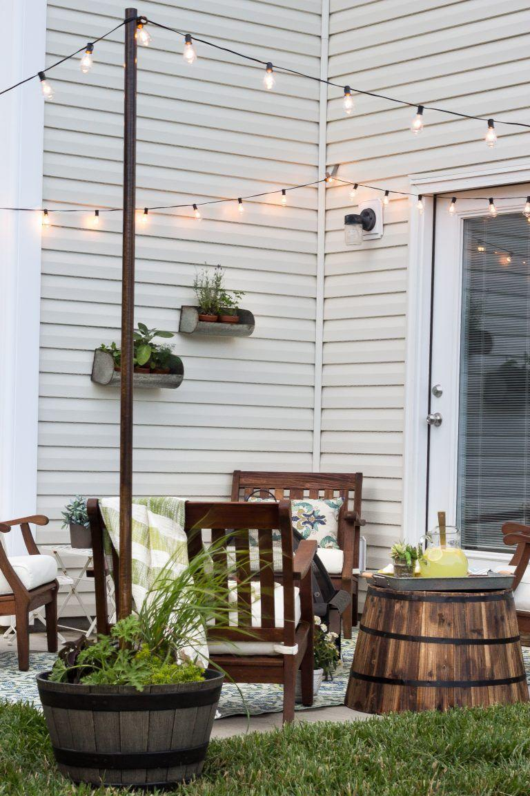 """<p>Don't have an existing structure to hang outdoor string lights from? Cement poles to the bottom of planters anchored at each corner of your patio.</p><p><strong>See more at <a href=""""https://www.blesserhouse.com/2016/05/decorate-small-patio.html"""" rel=""""nofollow noopener"""" target=""""_blank"""" data-ylk=""""slk:Bless'er House"""" class=""""link rapid-noclick-resp"""">Bless'er House</a>.</strong></p><p><strong><a class=""""link rapid-noclick-resp"""" href=""""https://www.amazon.com/addlon-Commercial-Weatherproof-Heavy-Duty-Decorative/dp/B07CKRM6M8/ref=sr_1_5?tag=syn-yahoo-20&ascsubtag=%5Bartid%7C10050.g.3404%5Bsrc%7Cyahoo-us"""" rel=""""nofollow noopener"""" target=""""_blank"""" data-ylk=""""slk:SHOP STRING LIGHTS"""">SHOP STRING LIGHTS</a><br></strong></p>"""