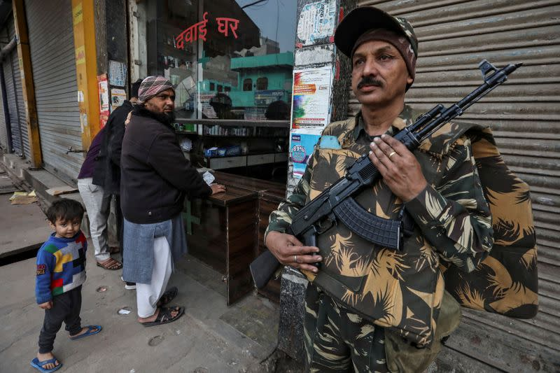 A paramilitary soldier stands guard outside a chemist shop at a riot affected area after clashes erupted between people demonstrating for and against a new citizenship law in New Delhi