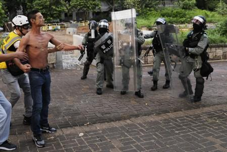 A shirtless anti-government protester is being prevented from confronting riot police officers during a protest at Tai Po district, in Hong Kong