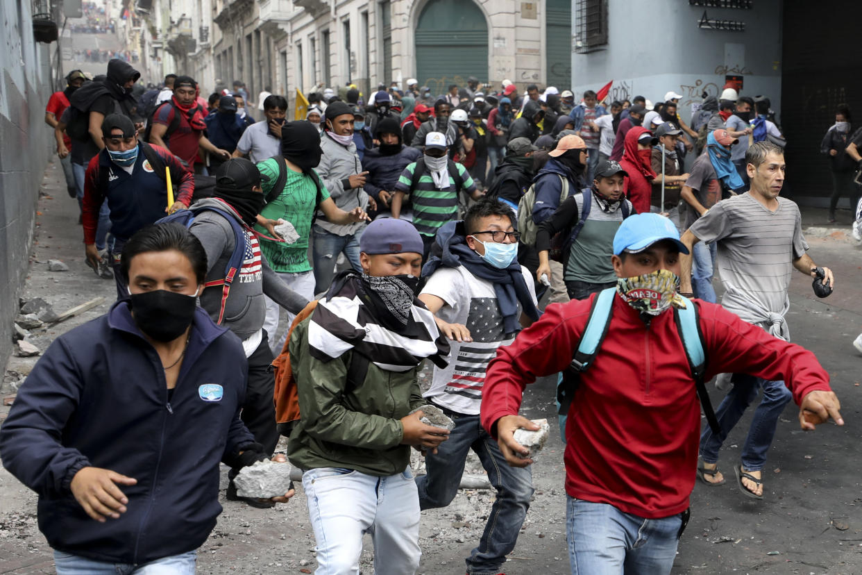 Anti-government protesters, stones in hand, run during clashes in downtown Quito, Ecuador, Oct. 8, 2019. (Photo: Fernando Vergara/AP)