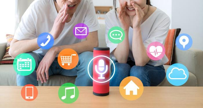 Icons for calls, music, groceries, and more float around a smart speaker to which two people are talking.