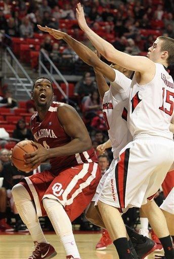 Oklahoma's Andrew Fitzgerald tries to shoot under pressure from Texas Tech's Robert Lewandowski(15) and Jaye Crockett, center, during their NCAA college basketball game in Lubbock, Texas, Saturday, Feb. 11, 2012. (AP Photo/Lubbock Avalanche-Journal, Zach Long) ALL LOCAL TV OUT