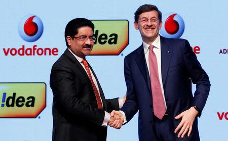 Kumar Mangalam Birla, chairman of Aditya Birla Group, shakes hands with Vittorio Colao, CEO of Vodafone Group, after a news conference in Mumbai