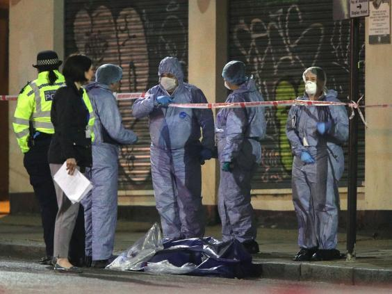 Forensic officers and police at the scene in Stoke Newington, north-east London after a man was stabbed to death on 17 April (PA)