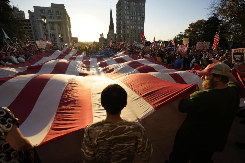 Supporters of President Donald Trump unfurl a giant American flag outside the Pennsylvania State Capitol, Saturday, Nov. 7, 2020, in Harrisburg, Pa., after Democrat Joe Biden defeated Trump to become 46th president of the United States. (AP Photo/Julio Cortez)