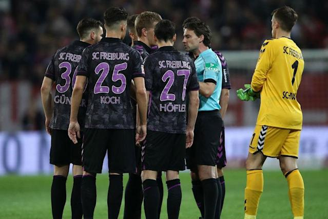 The players of Mainz 05 and Freiburg were ordered back onto the pitch having gone to the changing room at halftime because the video assistant referee (VAR) awarded a penalty for a handball in an eventful Bundesliga game on Monday.