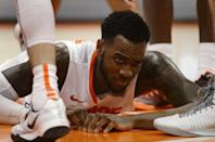 Syracuse's Rakeem Christmas grimaces after taking a hard fall to the floor against Colgate during the second half of an NCAA college basketball game in Syracuse, N.Y., Monday, Dec. 22, 2014. (AP Photo/Kevin Rivoli)