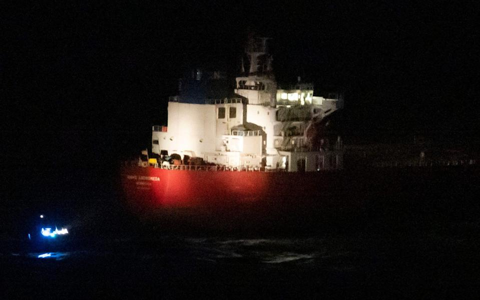 CAPTION UPDATE © Licensed to London News Pictures. 25/10/2020. Isle of Wight, UK. A police boat lights up the hull of the oil tanker Nave Andromeda as a rescue mission gets underway off the Isle of Wight in the English Channel. It is being reported that stowaways have seized the ship which sailed from Lagos and was supposed to berth at Southampton this morning. Photo credit: - Peter Macdiarmid/LNP