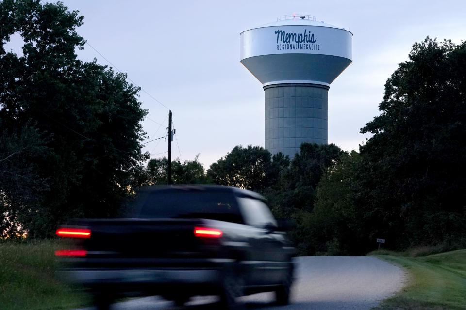 A truck drives down a rural road near a water tower marking the location of the Memphis Regional Megasite on Sept. 24, 2021, in Stanton, Tenn. Ford Motor Co. and SK Innovation of South Korea plan to build three new electric-vehicle battery factories and an auto assembly plant by 2025 in Tennessee and Kentucky. The industrial site in Stanton will be the location for a factory to produce electric F-Series pickups and a battery factory. (AP Photo/Mark Humphrey)